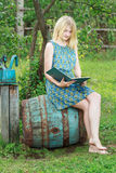 Barefoot student girl in garden is reading book with blue cover Royalty Free Stock Image