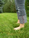 Barefoot in the summertime. Young woman standing barefoot in grass Stock Images
