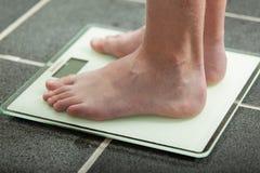Barefoot teenage boy weighing himself Royalty Free Stock Photo