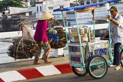 Barefoot Vietnamese mature woman in conical Asian hat carrying wood in busy street on February 13, 2012 in My Tho, Vietnam Royalty Free Stock Image