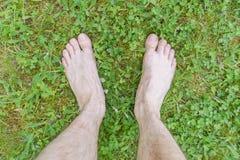 Barefoot walking. Feet of a man on green grass stock image