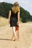 Barefoot woman. Portrait of a barefoot woman holding her red sandals royalty free stock photos