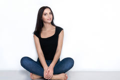 Barefoot woman in casual wear sitting on floor Stock Photography