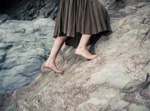 Barefoot woman climbing rock Royalty Free Stock Photos