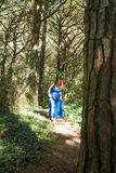 Barefoot woman dressed in blue walking alone through forest Stock Images