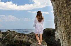 Barefoot woman enjoying the solitude of the coast Stock Photo