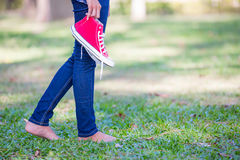 Barefoot woman holding shoes Stock Photo