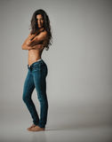 Barefoot woman in jeans and bare chest. Barefoot pretty single woman in tight blue jeans and folded arms over bare chest. Includes copy space royalty free stock images