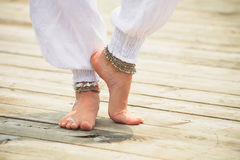 Barefoot woman legs  boho summer fashion. Closeup of young woman barefoot legs in white clothes and anklets boho summer fashion style on wooden pontoone by the Stock Images