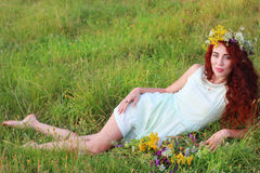 Barefoot woman lies in grass on meadow Stock Photos