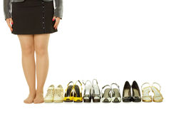 Barefoot woman and lots of shoes Royalty Free Stock Photos