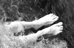 Barefoot woman in the pool of the spa with balck and white effec. Barefoot woman in the pool of the spa during a session of massage therapy with black and white Royalty Free Stock Photography