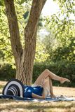 Barefoot woman relaxing outdoors in the garden. In her sunhat lying on the grass in the shade of a tree with a long cold drink in her hand Royalty Free Stock Images