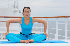 Barefoot woman sits and does exercise. Beautiful barefoot woman wearing in sports suit sits on cruise liner deck and does exercise stock images