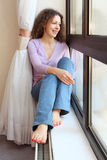 Barefoot woman sits on windowsill Stock Images