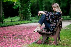 Barefoot woman is sitting on a bench at alley with blossom trees. In springtime royalty free stock image
