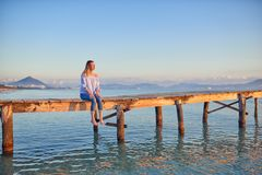 Barefoot woman sitting on a rustic wooden coastal pier. Or boardwalk at sunset with her legs dangling above the sea facing towards the setting sun Royalty Free Stock Images