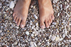 Barefoot woman standing on the pebbles or stones Stock Photo