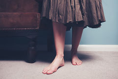 Barefoot woman standing by sofa. A barefoot woman is standing by a sofa royalty free stock photography
