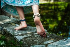 Barefoot woman walk boho fashion style  with jewelry outdoor. Barefoot woman walk  summer boho fashion style  with jewelry anklets and rings on stone outdoor Royalty Free Stock Images
