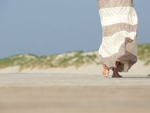 Barefoot woman walking away at the beach. Rear view close up barefoot woman walking away at the beach stock photography