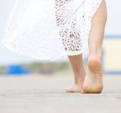 Barefoot woman walking away. Close up portrait of a barefoot woman walking away stock photo