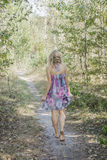 Barefoot woman walking through the forest. Stock Photos