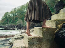 Barefoot woman walking up steps in nature Stock Image