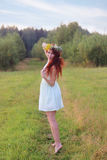 Barefoot woman in wreath and short dress poses on meadow Stock Image