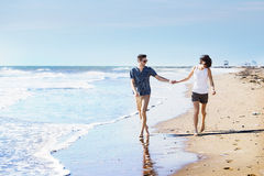 Barefoot young couple walking on a beach Stock Photo