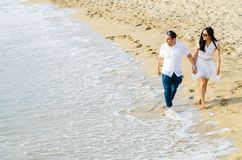 Barefoot young couple walking hand in hand along a beach at the edge of the surf. stock photo