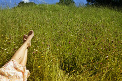 Barefoot of young girl lying on meadow Stock Images