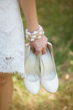 Barefoot young girl wearing white beautiful dress holding shoes Royalty Free Stock Photography