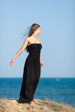 Barefoot young woman in black at the sea Stock Image