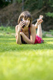 Barefoot young woman chatting on a mobile phone as she lies on h Royalty Free Stock Photos