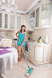 Barefoot young woman mopping the floor. Barefoot young woman in a trendy blue summer dress mopping the floor in the kitchen with a squeegee mop Stock Photography