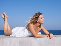 Barefoot young woman in short white sleeveless dress sunbathes w. Barefoot girl on seafront. Young woman in short white sleeveless dress sunbathing on seashore royalty free stock photos