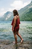 Barefoot young woman standing on rock looking at beautiful lake Royalty Free Stock Photography