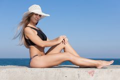 Barefoot young woman in sun hat sitting on concrete pier Royalty Free Stock Photography