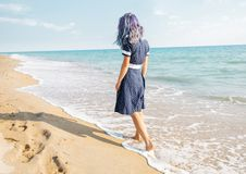 Barefoot young woman walking on shore. Unrecognizable barefoot young woman with blue hair in dress walking on shore near the sea royalty free stock photo