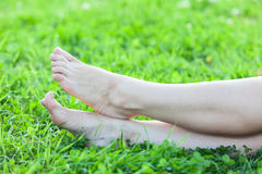 Barefooted attractive female feet on green grass Stock Photography