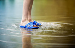 Barefooted baby feet in a puddle of rain in shales. Barefooted baby feet in a puddle of rain in shales royalty free stock images