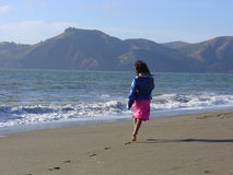 Barefooted beach girl. A young barefooted girl runs joyfully along a beach. Coastal mountains in the background. The girls face is not visible royalty free stock photo