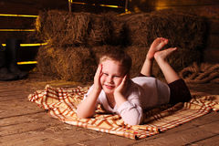 Barefooted boy in a hayloft. Kid in a white shirt lying on a rug in hay on the background of haystacks Royalty Free Stock Photography