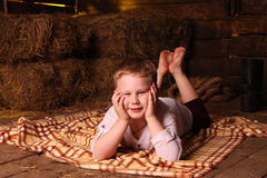Barefooted boy in a hayloft. Kid in a white shirt lying on a rug in hay on the background of haystacks Royalty Free Stock Image
