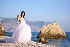 Barefooted bride. Portrait of beautiful young bride on the sea coast Stock Photo