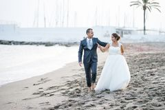 Barefooted newlywed couple walking on the beach. Barefooted bride and groom enjoying a walk on the beach stock photography