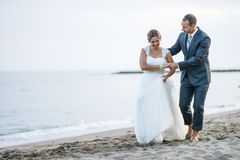 Barefooted newlywed couple walking on the beach. Barefooted bride and groom enjoying a walk on the beach stock photo
