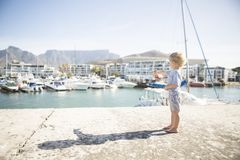 Barefooted Child Points to Luxury Yacht in Harbour. A barefooted child unrecognizable in pastel blue points from a jetty to a luxury yacht anchored in the royalty free stock photography