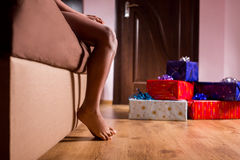 Barefooted child sitting beside presents. Stock Images